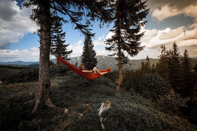 Woman resting in a red hammock outdoors.