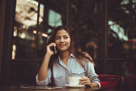Young woman on the phone at a cafe.